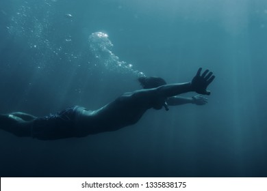 Freediver young man swimming underwater and using breaststroke technique.