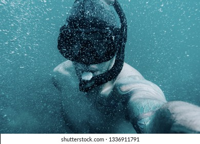 Freediver young man taking selfie portrait underwater, point of view.