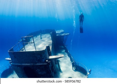 Freedivers swimming through a large underwater shipwreck