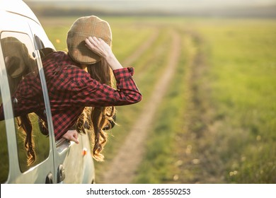 Freedom car travel concept - woman relaxing out of window in a car. Road trip
