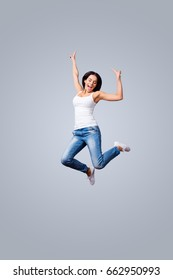 Freedom, carefree, fun, summer mood. Excited young brunette is jumping and showing peace signs. She is in jeans and casual white singlet