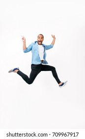 Freedom, carefree, fun, summer mood. Excited young african man is jumping and showing peace signs. He is in casual jeans outfit and gumshoes, on pure white background