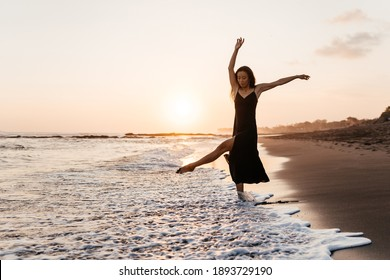 Freedom Chinese woman feeling free dancing in black elegant dress at beach sunset. Healthy living Asian girl on summer travel vacation. Success, happiness, mindfulness concept.