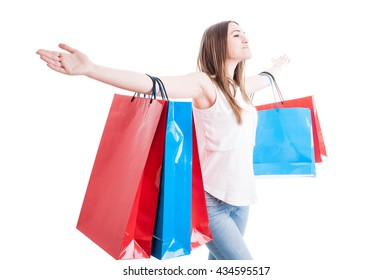 Freedom concept with beautiful shopaholic standing with arms wide open enjoying her leisure isolated on white background