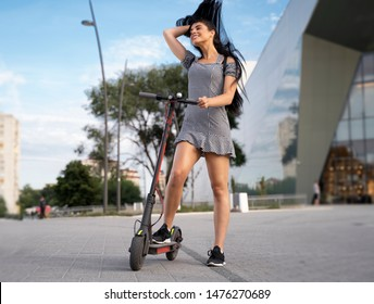 Freedom concept, cool young girl flicking hair back while standing on electric  scooter