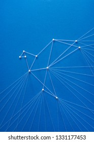 Freedom concept on blue background. Network of pins and threads in the shape of a bird breaking free symbolising team effort, hope, purity and spirituality.