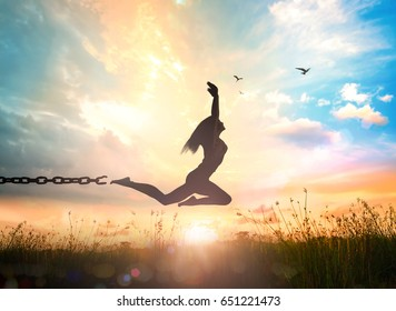 Freedom concept: Silhouette of a girl jumping and broken chains at autumn sunset meadow with her hands raised
