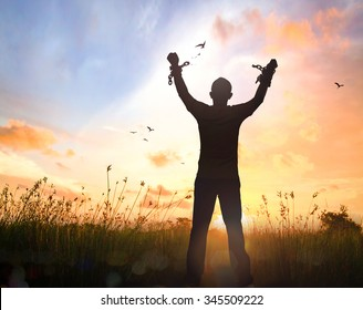 Freedom concept: Silhouette human hand broken chains against twilight sky autumn sunset background