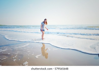 Freedom concept. Smile Freedom and happiness woman on beach. She is enjoying serene ocean nature during travel holidays vacation outdoors.Technical Writing light synthesizer. vintage and hipster tone.
