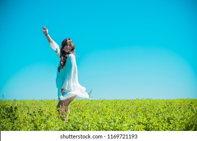 Freedom concept. Young happy woman in green field, evening light. Blue sky behind. Beauty Girl Outdoors enjoying nature. Beautiful Teenage Model girl in white dress running on the meadow