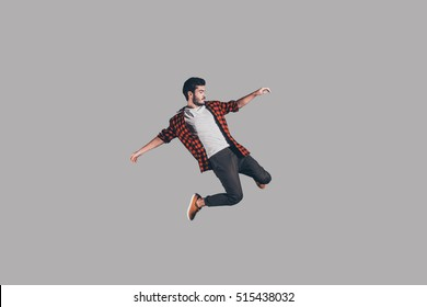 Freedom in every move. Mid-air shot of handsome young man jumping and gesturing against background