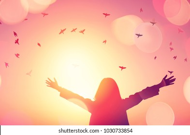 Freedom and feel good concept. Copy space of silhouette woman rising hands on sunset sky double exposure colorful bokeh light and birds fly background. Vintage tone filter effect color style.
