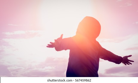 Freedom and feel good concept. Copy space of silhouette man rising hands on sunset sky background with sun light. Vintage tone filter effect color style.
