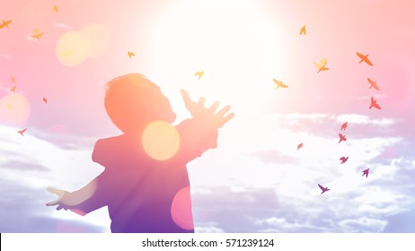 Freedom feel good and travel adventure concept. Copy space of silhouette man rising hands on sunset sky double exposure colorful bokeh and bird fly background. Vintage tone filter effect color style.