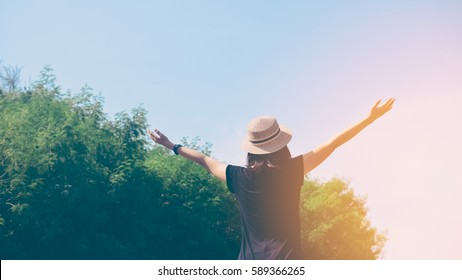 Freedom feel good and travel adventure concept. Copy space silhouette woman rising hands in nature green leaf with blue sky background. Vintage tone filter effect color style.