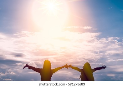 Freedom feel good and travel adventure concept. Copy space of silhouette women rising hands on blue sky and white cloud with sun light background. Vintage tone filter effect color style.
