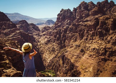 Freedom female wanderlust standing with raised hands enjoying majestic mountain landscape. Hipster young girl explore world. Summer vacation. Impressive nature. Travel lifestyle. Ecotourism concept