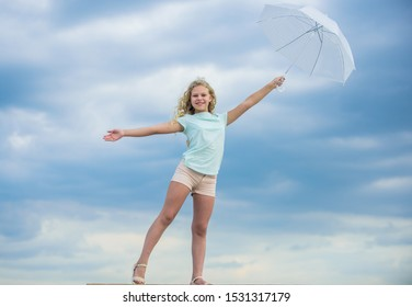 Freedom and freshness. Anti gravity concept. Enjoying ease. Carefree child outdoors. Weather forecast. Ready for any weather. Weather changing. Fresh air. Girl with umbrella cloudy sky background.