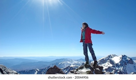 Freedom! Girl over a snow capped peaks with outstretched arms.