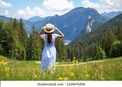 Freedom girl standing with beautiful view from alpine mountain holding her hat on a summer day