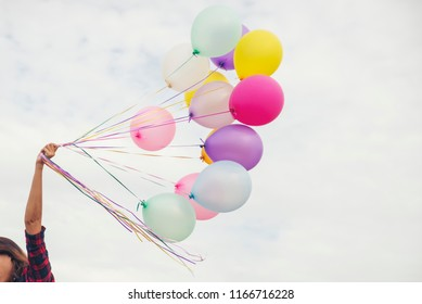Freedom Hand,Let it go and Release concept.Birthday balloon Holding by Happy Beautiful women in summer carnival.Colorful of multicolored balloons floating in Happy New Year Party,vintage filter effect