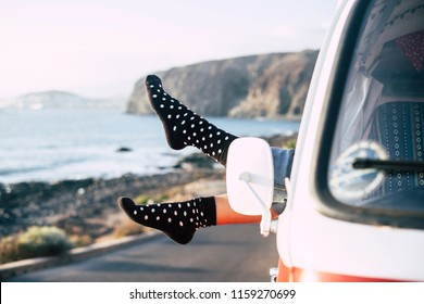 freedom and happiness concept image with pair of female feet out of the window of a classic van parked near the coast. ocean view for alternative and positive lifestyle. travel and enjoy the world