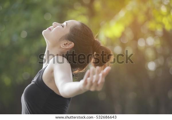 緑の背景に太陽の光で手を上げ、深呼吸。