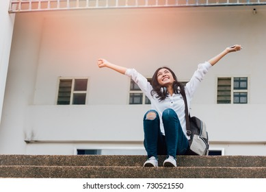 Freedom happy girl college student feeling alive and free in nature breathing clean and fresh air on the campus.showing happiness with arms raised up.learning, education and school concept