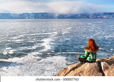 Freedom happy redhead woman sitting in meditation enjoying a view of a frozen lake Baikal surface. Winter tourism concept