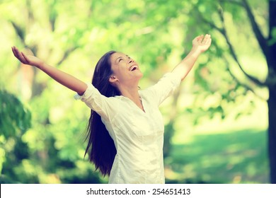 Freedom happy woman feeling alive and free in nature breathing clean and fresh air. Carefree young adult dancing in forest or park showing happiness with arms raised up. Spring allergies concept.