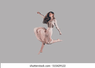 Freedom in her every move. Studio shot of attractive young woman hovering in air