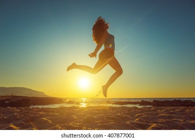 Freedom, lifestyle concept. Happy girl jumping on the beach against beautiful sunset.