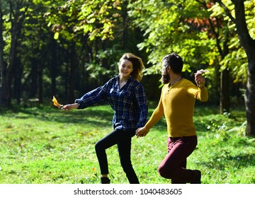 Freedom and love concept. Man and woman with happy faces on autumn trees background. Couple in love walks in park. Girl and bearded guy or happy lovers on a date run holding hands
