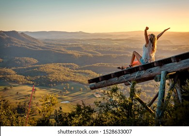 Freedom loving woman feeling the exhilaration high above the valley