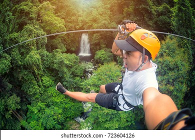 Freedom Male Tourist Wearing Casual Clothing On Zip Line Or Canopy Experience In Laos Rainforest, Asia