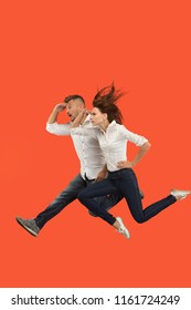 Freedom in moving and forward motion. The happy young couple jumping and gesturing against red studio background. Runnin girl and man in motion or movement. Human emotions and facial expressions
