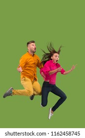 Freedom in moving and forward motion. The happy surprised young couple jumping a against green studio background. Runnin girl and man in motion or movement. Human emotions and facial expressions