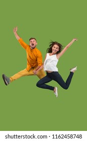 Freedom in moving and forward motion. The happy young couple jumping a against green studio background. Runnin girl and man in motion or movement. Human emotions and facial expressions