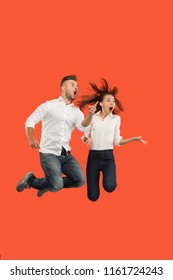 Freedom in moving and forward motion. The surprised young couple jumping and gesturing against red studio background. Runnin girl and man in motion or movement. Human emotions and facial expressions