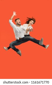 Freedom in moving. The happy young couple jumping and gesturing against red studio background. Runnin girl and man in motion or movement. Human emotions and facial expressions concept