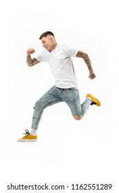 Freedom in moving. Mid-air shot of handsome happy young man jumping and gesturing against white studio background. Runnin guy in motion or movement. Human emotions and facial expressions concept