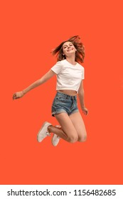 Freedom in moving. Mid-air shot of pretty happy young woman jumping and gesturing against orange studio background. Runnin girl in motion or movement. Human emotions and facial expressions concept