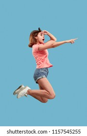 Freedom in moving. Mid-air shot of pretty happy young woman jumping and pointing by finger against blue studio background. Runnin girl in motion or movement. Human emotions and facial expressions
