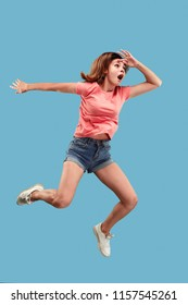 Freedom in moving. Mid-air shot of pretty happy surprised young woman jumping against blue studio background. Runnin girl in motion or movement. Human emotions and facial expressions concept