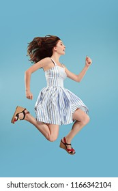 Freedom in moving. Mid-air shot of pretty happy young woman jumping and gesturing against blue studio background. Runnin girl in motion or movement. Human emotions and facial expressions concept