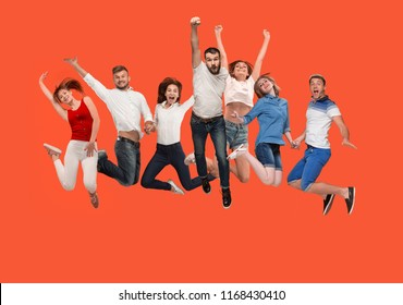 Freedom in moving. Mid-air shot of pretty happy young man and women jumping and gesturing against studio background. Runnin girl in motion or movement. Human emotions and facial expressions concept