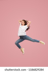 Freedom in moving. Mid-air shot of pretty happy young woman jumping and gesturing against pink studio background. Runnin girl in motion or movement. Human emotions and facial expressions concept