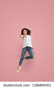 Freedom in moving. Mid-air shot of pretty happy young woman jumping and pointing to camera against pink studio background. Runnin girl in motion or movement. Human emotions and facial expressions