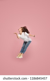 Freedom in moving. Mid-air shot of pretty happy young woman jumping and kissing against pink studio background. Runnin girl in motion or movement. Human emotions and facial expressions concept