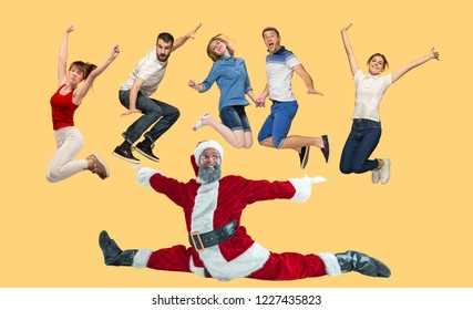 Freedom in moving. Mid-air shot of pretty happy young man and women jumping and gesturing against studio background. Runnin girl and Santa. Christmas and holiday concept